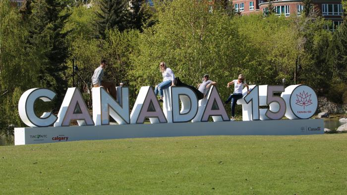 "3D-Schriftzug ""Canada 150"", auf dem Leute sitzen"