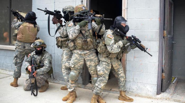 Bewaffnete Soldaten in Tarnanzügen und Atemschutz vor Gebäude