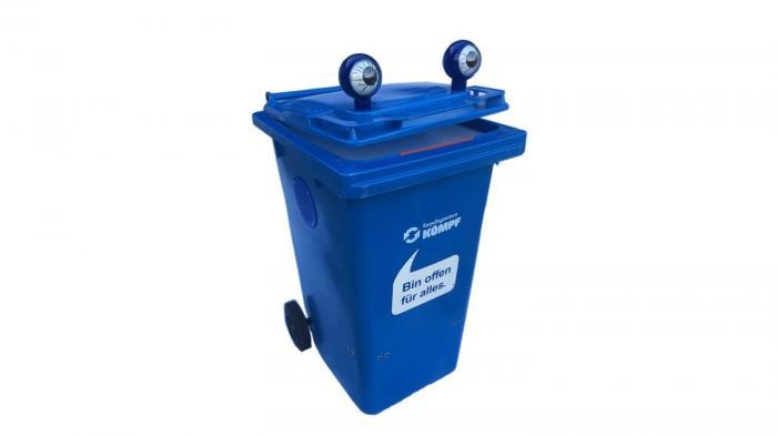 Eine blaue Mülltonne mit Augen vor weißem Hintergrund