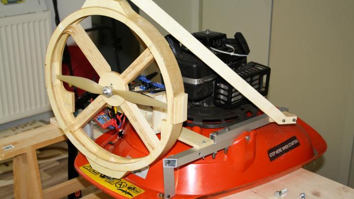 Ein roter Hoverboard-Rasenmäher auf einem Tisch, hinten ist ein Propeller im Rinaus Holz befestigt