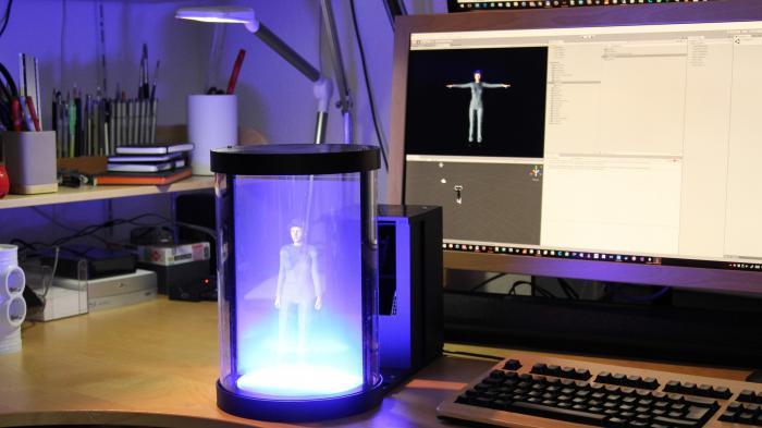 """Vor einem Bildschrim steht ein schwarzes Gehäuse, in dessen Licht steht eine """"holografische"""" Frauenfigur"""