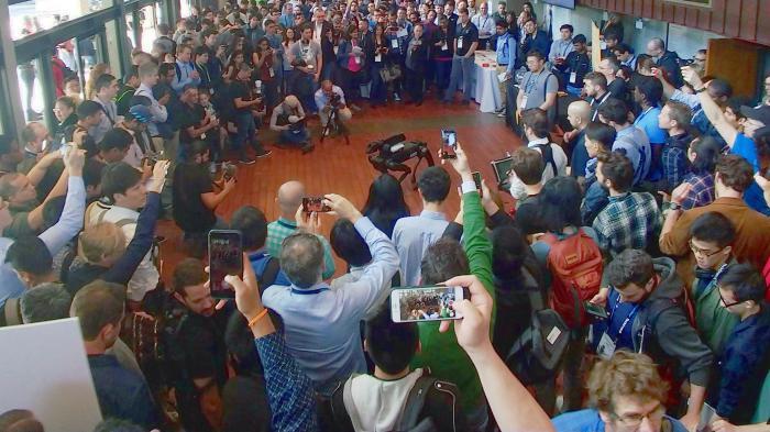 Eine Menschenmenge mit Smartphones und Kameras hat einen Kreis um den Roboter SpotMini gebildet