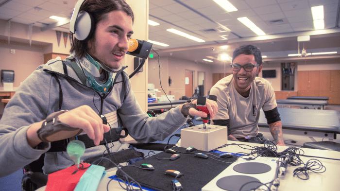Eine Person mit eingeschränkter Mobilität welche den Xbox Adaptive Controller bedient
