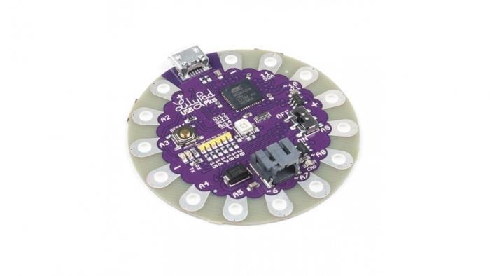 Lilypad USB: ein rundes lila Board mit runden Anschlüssen für leitfähiges Garn