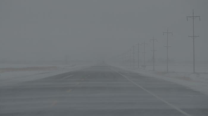 Fahrbahn mit Nebel und Schneeverwehungen