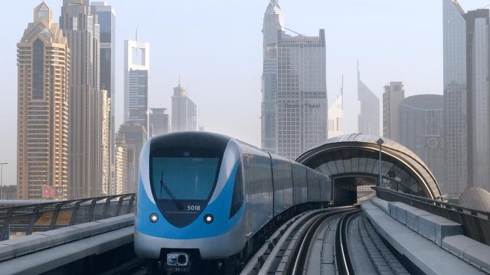 U-Bahn-Zug auif Viadukt, dahinter die Skyline Dubais