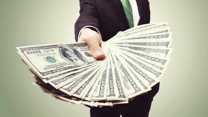 Business,Man,Displaying,A,Spread,Of,Cash,Over,A,Green