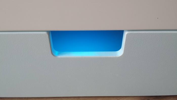 Aus einer weißen Schublade leuchtet ein türkises Licht
