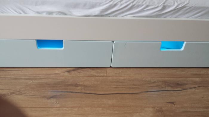 Aus zwei weißen Schubladen unter einem IKEA-Babybett leuchtet es türkis