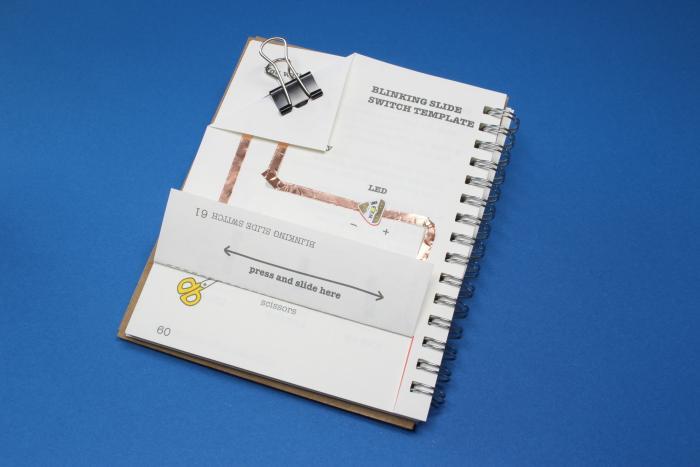 Eine Seite aus einem Ringbuch, auf der Kupferkabel und eine LED kleben
