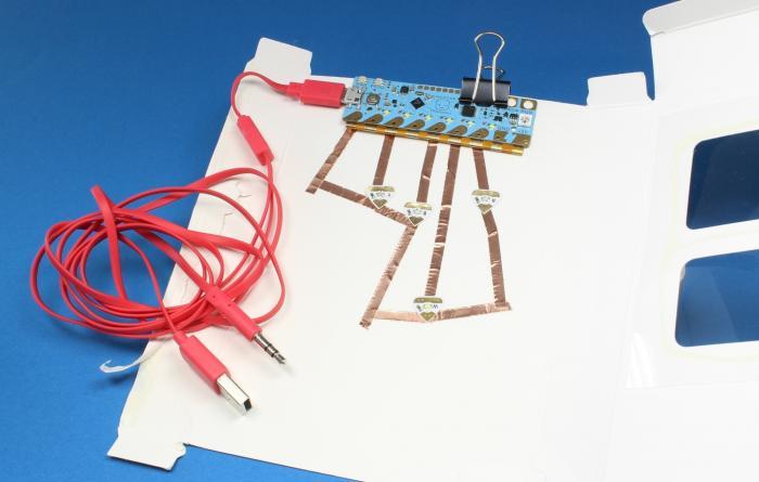 Auf einem weißen Papier ist ein blauer Mikrocontroller festgeklippt. An ihm hängt ein rotes Kabel.