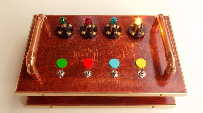 Blick auf ein Schaltpult aus zwei übereinander gestapelten Holzplatten. Auf der oberen sind vier bunte Leuchten, daneben vier Marker in der gleichen Farbe und vier Schalter. Ein Schalter ist umgelegt und das (gelbe) Licht leuchtet daneben auf.