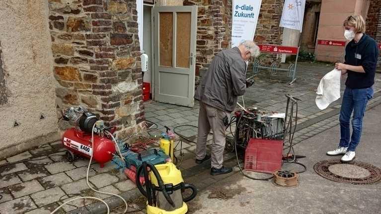 Vor einem Gebäude stehen ein älterer Mann und eine junge Person mit einigen technischen Geräten.