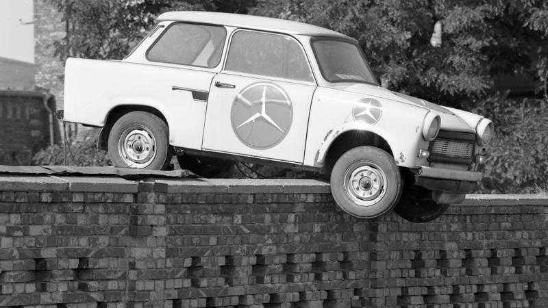 Trabi mit großem Mercedes-Stern.Aufkleber hängt über Mauer