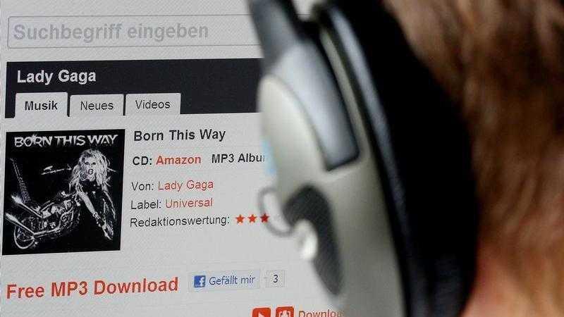 """Person mit Kopfhörer vor Bildschirm, der eine Webseite mit """"MP3"""" zeigt"""