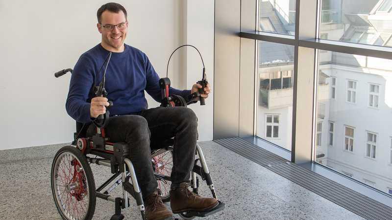 Mann in Rollstuhl mit Kurbeln