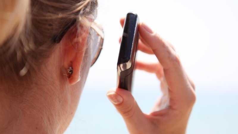 Frau führt Handy ans Ohr