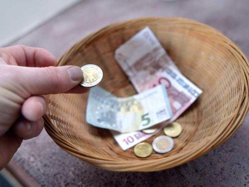 Körberl mit Geldscheinen und Münzen, eine Hand wirft gerade eine Münze hinzu