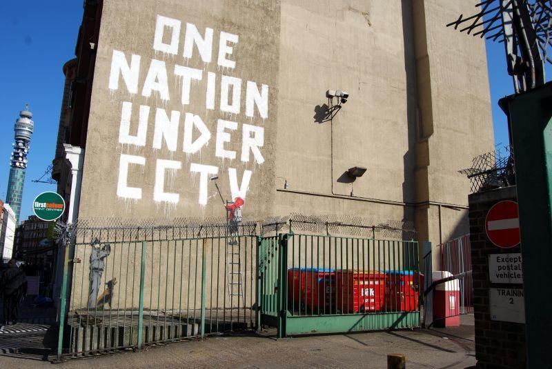 """Feuermauer mit Aufschrift """"One Nation Under CCTV"""""""