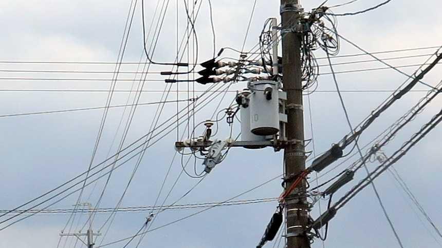 Mast mit Gewirr an Strom- und Telekommunikationskabeln