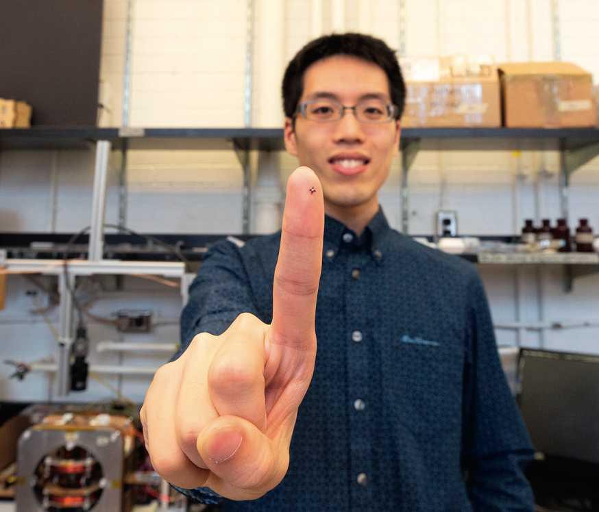 Wissenschaftler Tianqi Xu zeigt auf seiner Fingerkuppe einen Mikroroboter-Greifer, mit dem die Forscher in einer Mikrofabrikation kleinste Teile manipulieren.