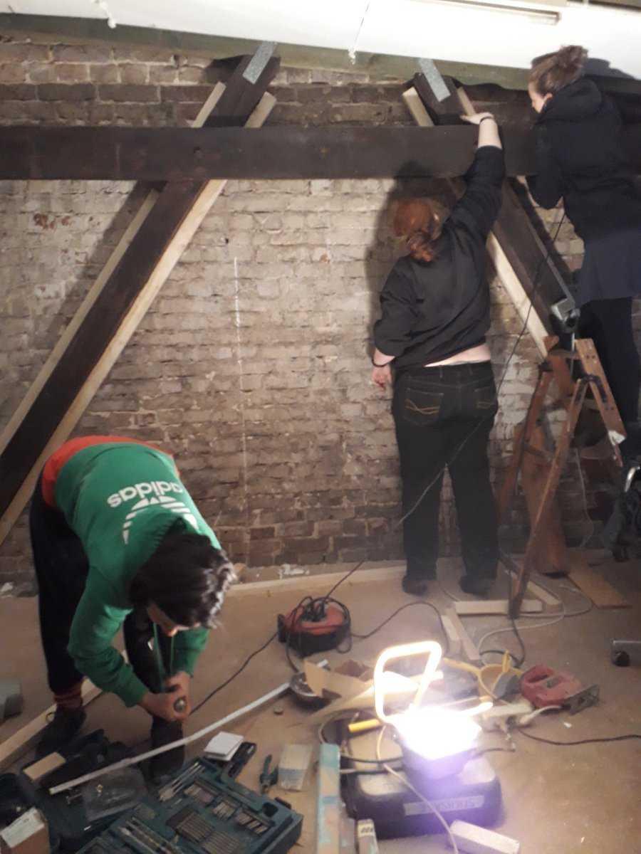Drei Leute halten Werkzeuge und Holzbalken in einem unverputzten Raum